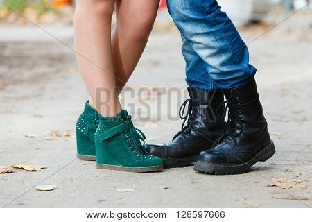 Fashion footwear dating romance love youth outdoor concept. Young lady meeting rough boy. Elegant girl in glamour shoes with man in jeans boots.