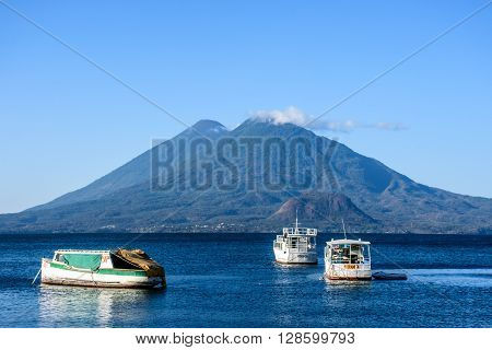 Lake Atitlan, Guatemala - April 3 2016: Early morning light on boats at anchor in front of volcanoes Atitlan & Toliman on Lake Atitlan, Guatemala.