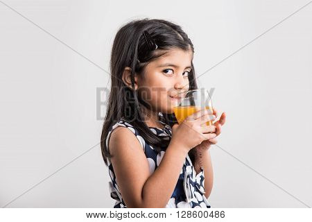 portrait of indian small girl drinking mango juice or fruit juice in a glass, asian girl and a glass of juice, indian small girl holding a glass of mango juice or orange juice on blue background