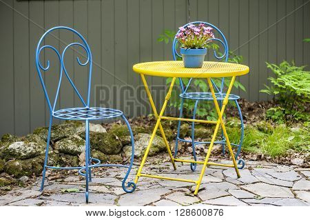Table chairs centerpiece ready for casual garden party