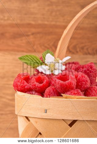 Basket with fresh raspberries, against wooden background