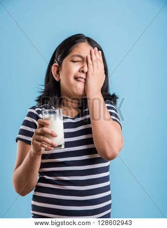 portrait of sad indian girl with a glass of milk, asian girl drinking milk in a glass with sad expressions, portrait of small girl holding a glass of milk over blue background