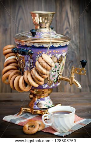Russian traditional samovar with colorful donuts and bagels with a cup of tea on a wooden background
