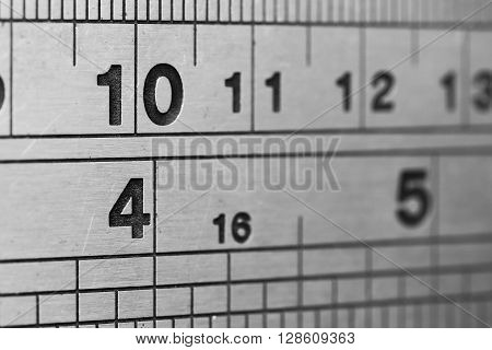 A section of a metal ruler, showing centimetres and inches, in closeup