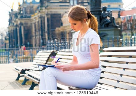 Woman tourist writes his impressions in a diary, Dresden, Germany