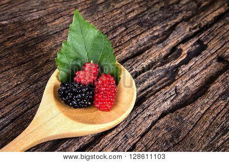 mulberry fruit in the wooden spoon on a wood plate