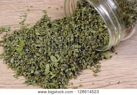Heap of dried marjoram spilling out of glass jar on wooden background seasoning for cooking concept for healthy nutrition