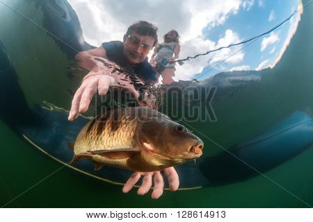 The underwater scenes. Fisherman in a boat catches a fish under water