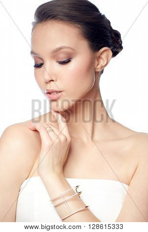 beauty, jewelry, wedding accessories, people and luxury concept - beautiful asian woman or bride with golden ring and bracelet