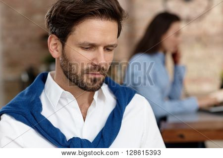 Closeup portrait of thoughtful young businessman looking down.