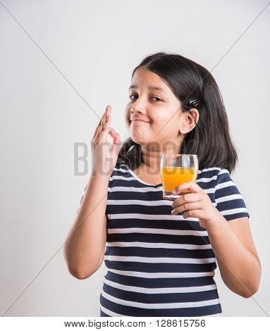 portrait of indian small girl drinking mango juice or fruit juice or cold drink in a glass, asian girl and a glass of juice, indian small girl holding a glass of mango juice or orange juice on blue background