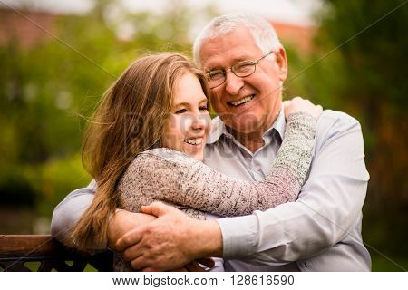 Happy grandfather hugging with his teenage granddaughter outdoor in nature ** Note: Shallow depth of field