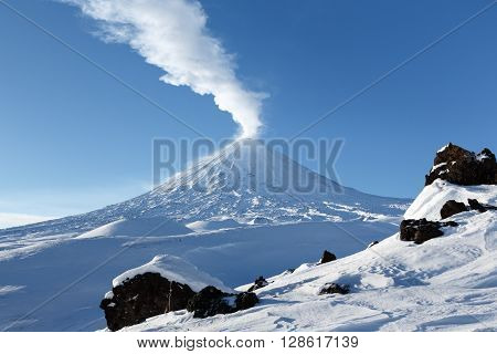 Beautiful winter volcanic landscape of Kamchatka: view of eruption active Klyuchevskoy Volcano (Klyuchevskaya Sopka) in clear weather sunny day. Eurasia Russia Far East Kamchatka Region Klyuchevskaya Group of Volcanoes.