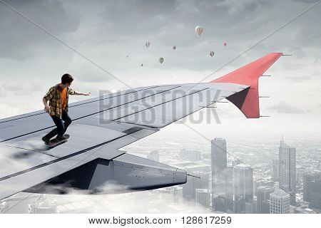 Guy sakting on airplane wing