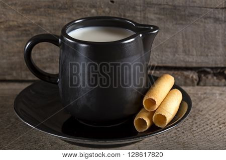 Milk cup with sweet corn rolls on plate with wooden background