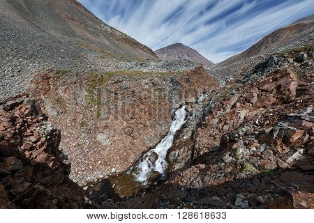 Scenic Kamchatka mountain landscape: beauty view of mountain river into steep cliffs on sunny day. Eurasia Russian Federation Far East Kamchatka Peninsula.
