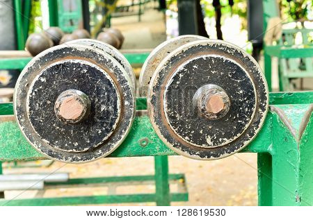 Selective focus of old dumbbell. Outdoor view (dumbbell, rust, weights)