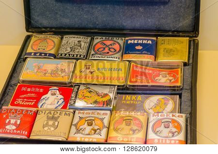 HAGEN NRW GERMANY - JULY 24 2014: Hagen Germany antique suitcases with various tobaccos cans packed up.