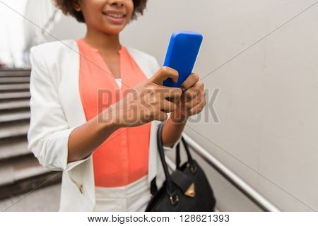 business, technology, communication and people concept - close up of young smiling african american businesswoman with smartphone and handbag texting walking downstairs to city subway