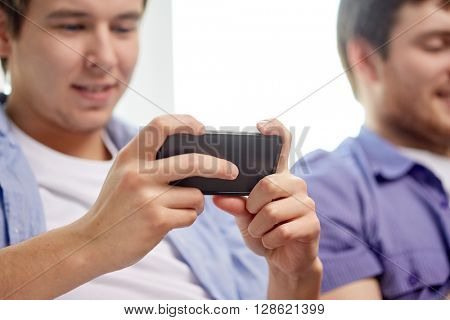 friendship, technology and people concept - close up of happy smiling male friends with smartphones texting or playing games at home