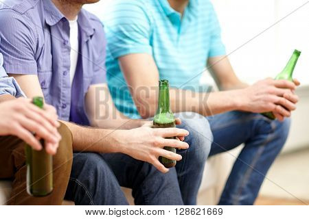 friendship, leisure, people and alcohol concept - close up of happy male friends drinking beer at home
