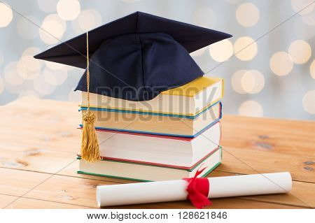 education, school, graduation and knowledge concept - close up of books and mortarboard with diploma on wooden table over holidays lights background