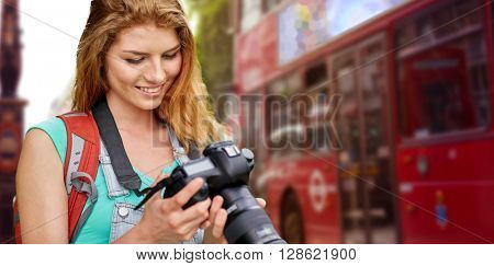 travel, tourism and people concept - happy young woman with backpack and camera photographing over london city street background