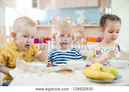 Funny little kids eating from plates in day care centre