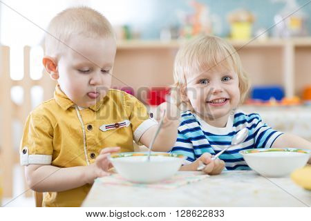 Two funny smiling little kids eating in kindergarten