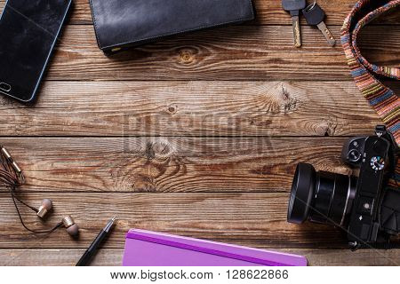 Travel concept - headphones, camera,  sketchbook, purse, pencil and keys on wooden background.