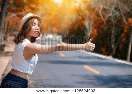 Portrait of a beautiful young Asia woman hitchhiking on the road.