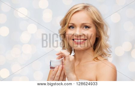beauty, people, skincare and cosmetics concept - happy woman with cream jar over holidays lights background