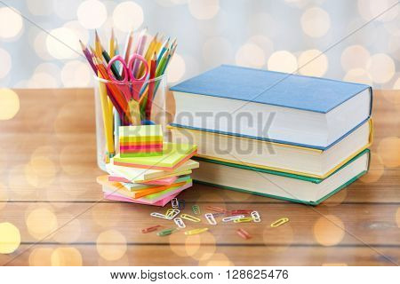 education, school supplies and object concept - close up of stand or glass with writing tools and book with scissors on wooden table over holidays lights background