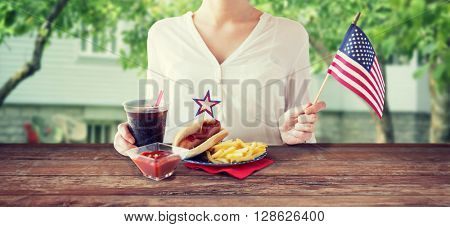independence day, celebration, patriotism concept - close up of woman hands with hot dog and french fries holding american flag and cola drink on 4th july party over summer house background