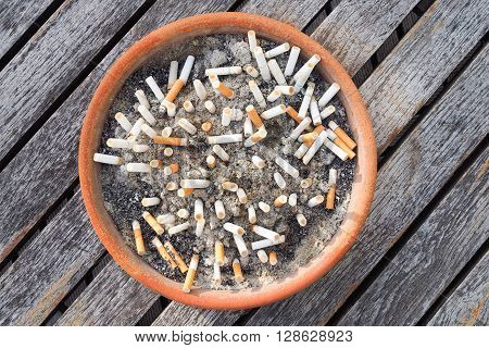 Cigarette butts in the ashtray on wood table background. The concept of World No Tobacco Day in 31 May stop smoking do not smoke quit smoking protect your health and other.