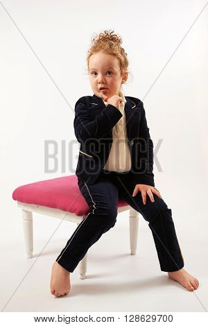 Little girl in black suit sitting and pouting