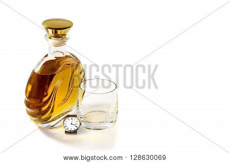 Bottle of whiskey with an empty tumbler and wrist watch on a white background