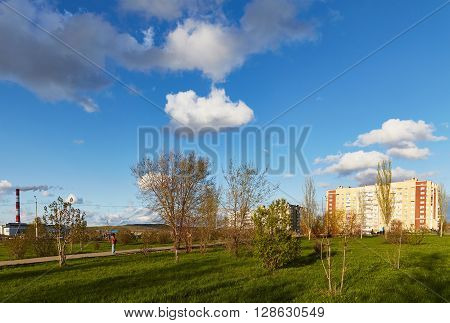 Saratov, Russia - 23 april 2016: City park among houses and the blue sky with beautiful clouds