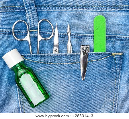 Basic set of manicure tools in blue jeans pocket. Nail and cuticle scissors, cuticle trimmer, nail clippers, nailfile, nail strengthener