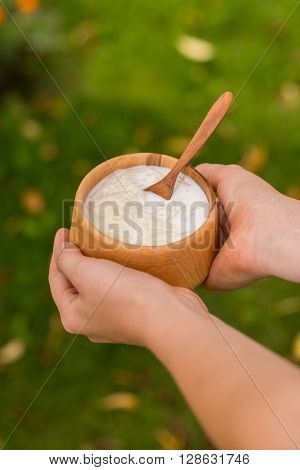 milk vermicelli in a handmade wooden bowl with handcarved wooden spoon outdoors
