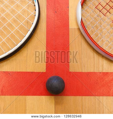 squash ball between two squash rackets on the court