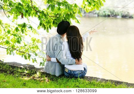 Young man and woman dating in the nature hugging each other.