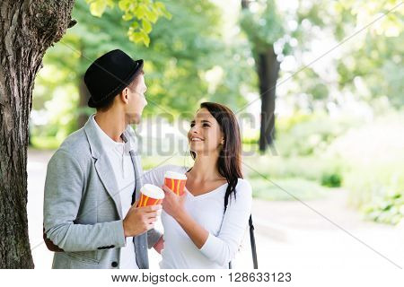 Young couple walking in the park together drinking coffee.