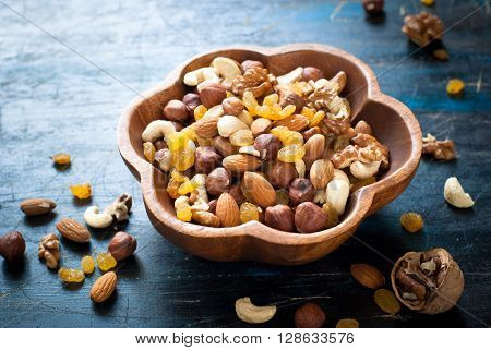 A Mix of variety nuts in a wooden bowl.