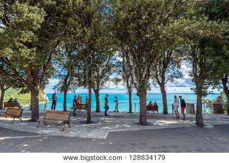 Sirolo, Italy - August 20, 2016: panoramic boardwalk with tourists in Sirolo Italy. Sirolo village features a medieval town centre which culminates in a square with view on the adriatic sea and on Mount Conero.