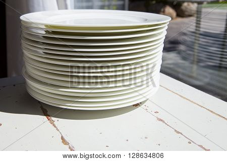 White plates piled on vintage table close to window