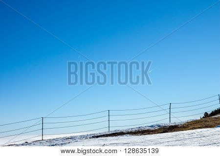 fence on top ot the mountain on blue sky background