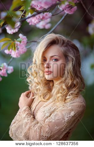Sensual young woman standing in sexy transparent dress at blossoming pink sakura tree in the garden. Beauty of woman and nature.Portrait of beautiful model with curly blonde hair