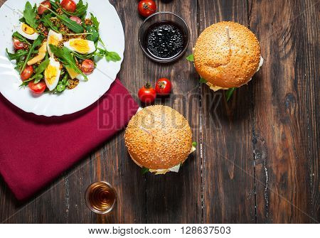 Fresh homemade burgers with a salad with arugula and alcohol on a dark background. View from above. Top view