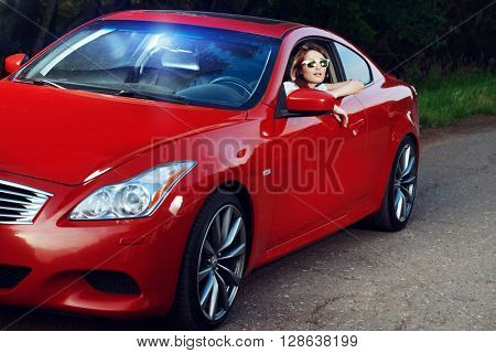 Happy young woman driving her red sports car. Traveling concept.